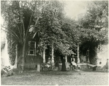 'Now the WVU State Agricultural Farm.' Ladies sit on the porch of a brick home obscured by trees.