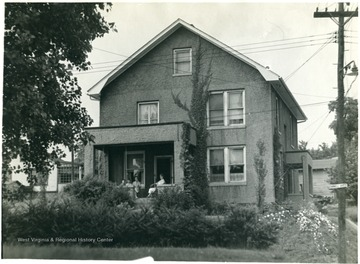 A few people sit on the porch of the Molby home on Cornell Avenue.