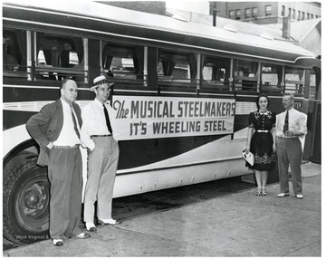 Four people are standing outside a Wheeling Steel, the Musical Steelmakers, bus, in Wheeling, West Virignia.