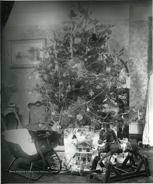 A christmas tree, Rocking Horse, Child's Sleigh, Doll House and other presents under the tree.