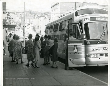 A bus from the Lake Shore System is dropping off some passengers at a bus stop on High Street in Morgantown, West Virginia.