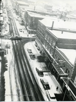 On a snowy winter day, a view of Walnut and High Streets in Morgantown, West Virginia. Odd Fellows is on the right corner.