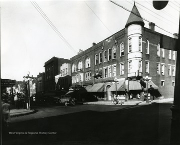 View of High Street from the corner of Pleasant Street and High Street in Morgantown, W. Va. Automobiles can be seen parked along side the street, and a person riding a bicycle near the corner.