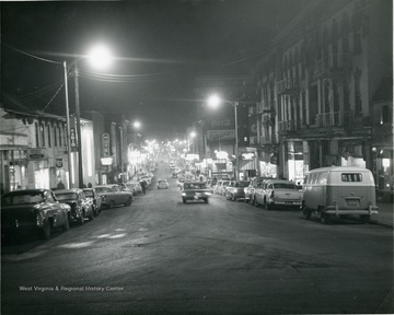 'North High Street looking South'. Taken after dark and the street lights are illuminated. Lights from stores and cars shine as well.