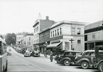 A woman waits to cross High Street at the corner of High Street and Fayette Street in Morgantown, W. Va.