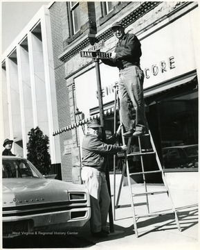 Two men attach the High St. sign and the Bank St. signs on High St.
