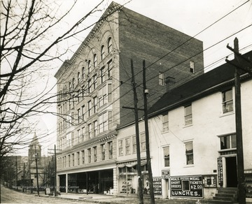 'High Street - corner of Fayette Street and High Street. Six story stone building is the old Strand Theater building, which burned down in 1927.'