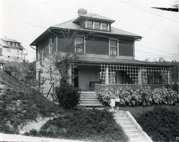 Front view of the residence of H. B. Allen in Morgantown, W. Va. Two children stand in front of the house on the walk way above the steps. Another house can be seen behind this residence.