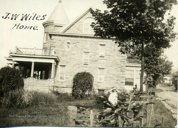 A young girl stands behind a bush near the J. W. Wiles home in Morgantown, W. Va. House has two balconies and two porches.