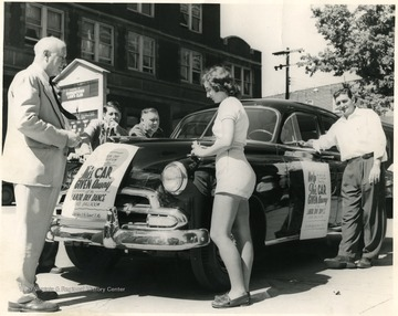 A girl fills out a piece of paper on the car while the men look on. Car to be given at the Labor Day Dance at the Elks Ballroom, Morgantown.