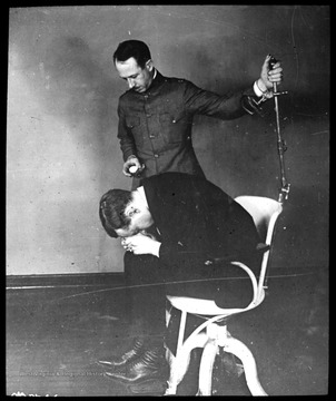 World War I Lantern Slide Show.  Slide No. 03 in group of originally numbered slides.  Physical examination of a recruit sitting in a chair.  This is apparently a balance test for a potential pilot.  Frame is labelled with text saying 'Visual Bureau, University of Pittsburgh.'  (negative no. 3-8246 is inscribed on slide)<br /><br />