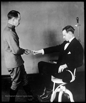 World War I Lantern Slide Show. Slide No. 05 in group of originally numbered slides. Physical examination of a recruit sitting in a chair. This is apparently a balance test for a potential pilot. Frame is labelled with text saying 'Visual Bureau, University of Pittsburgh.'  (negative no. 5-8237 is inscribed on slide)