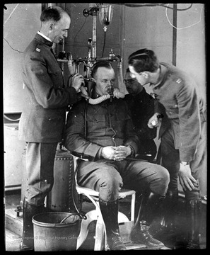 World War I Lantern Slide Show. Slide No. 06 in group of originally numbered slides. Physical examination of a recruit sitting in a chair breathing into a mask.  This is apparently a respiration test for a potential pilot. Frame is labelled with text saying 'Visual Bureau, University of Pittsburgh.'  (negative no. 6-19353 is inscribed on slide)