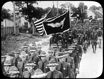 World War I Lantern Slide Show. Slide No. 08 in group of originally numbered slides.  American soldiers marching with flags.  Frame is labelled with text saying 'Visual Bureau, University of Pittsburgh.'  (negative no. 8-12199 is inscribed on slide)<br />