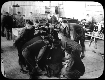 World War I Lantern Slide Show. Slide No. 09 in group of originally numbered slides.  Group of soldiers apparently learning about engine mechanics.  Frame is labelled with text saying 'Visual Bureau, University of Pittsburgh.'  (negative no. 9-450 is inscribed on slide)<br />