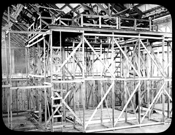 World War I Lantern Slide Show. Slide No. 12 in group of originally numbered slides.  Student pilots studying facsimile of ground in combat zone from top of scaffolding in flight simulation class.  Frame is labelled with text saying 'Visual Bureau, University of Pittsburgh.'  (negative no. 12-498 is inscribed on slide)<br />