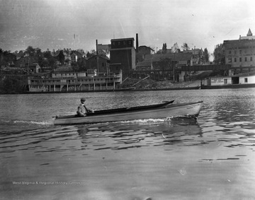 "A riverboat is visible along the shore near Walnut Street as a dapperly attired man cruises in the ""Nancy""."