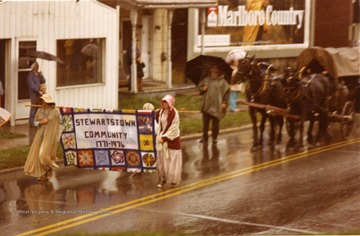 Two women carry the Stewartstown Community Banner in the Rain.