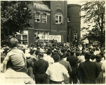 Crowds gather on the Courthouse Square to see Governor Wally Barron and actor Don Knotts who are standing at the podium.