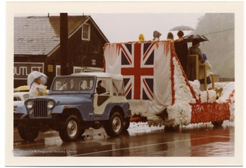 On a rainy day a jeep is pulling a float in the Monongalia Bicentennial Parade in Morgantown, West Virginia.