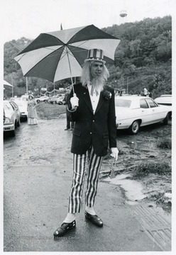 Man dressed as Uncle Sam holding a umbrella.