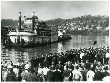 A crowd, including a marching band, gathered on the shore of the Monongahela River to watch the arrival of the Showboat Rhododendron.