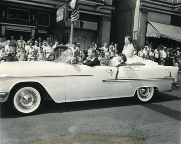 George Crago of the C.I.O. rides in a car in Labor Day Parade.