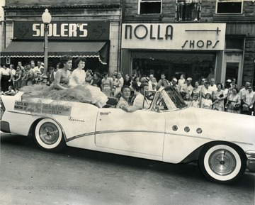 Two young ladies representing local labor unions ride in the back of a convertible in a parade.