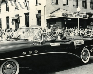Justice Bowers and Harley O. Staggers ride in a convertible in a Labor Day parade on High Street at the corner of High and Pleasant Streets.
