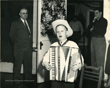 Child wearing a cowboy hat, singing, and playing an accordion. 'Labor Temple.'