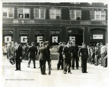 Men in uniform celebrating Veterans Day in front of the Monongalia County Courthouse in Morgantown, West Virginia. Roger's Florist Store is in the background.