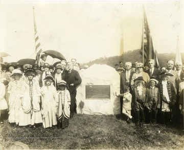 'Dedication and Unveiling of Monument at Pricketts Cemetery in Marion County, in memory of Colonel Zackquill Morgan and wife Drusilla. Boy standing with hand on monument and other hand to his nose is George M. Barrick, Jr., a direct descendant of Colonel Morgan, also took part in the unveiling. Date, Sunday, September 11, 1927. In the foreground pack of children on the right: Mr M. W. Harris, chairman of Monument Committee, Mrs. E. A Grose (Morgan), Max Mathers, Chairman of Program Committee. Roy Jake, speaker for the occasion of Dedication, Mr. Kerr. On the left, Dr. M. C. Kelley, representing Monongalia Historical Society. Back of Dr. Kelley, Earl Morgan (dedicatory address). Above in the names of the children who participated in unveiling of monument this data written by: Max Mathers, February 26, 1957.'