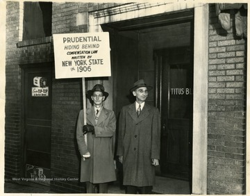 Two men stand in the doorway of the Titus Building.  One is holding a sign that reads 'Prudential Hiding Behind Compensation Law Written By New York State in 1906.'