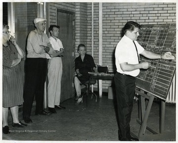 Dorthy Hiner, seated; Rex Everly, white shirt, standing; and Harold Wildman, wearing hat, standing; watch as votes are recorded on a chalk board.