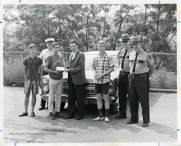 Winners of Road-E-O pose with police officers in this photograph.