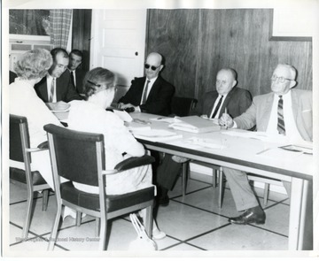 D. Earl Fisher (left, at head of table)and Lloyd Neilson (left with dark glasses) along with several others are attending a meeting.