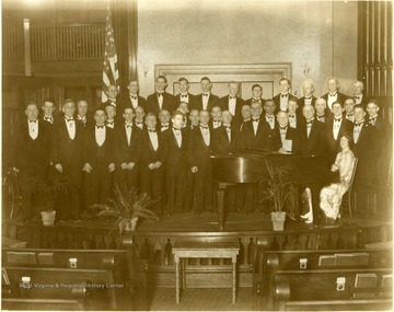 'The Apollo Club of local talent presented a concert at the Methodist Protestant Church on April 27, 1929. (Stars indicate deseased members as of April 27, 1949).' Members are as follows 1. Walter Corry* 2. Joe Hill 3. M. T. Sisler* 4. Harry Cole* 5. Delmar Smith 6. P. D. Chidester 7. Virgil Hall 8. Earl Martin* 9. Bob Jones* 10. David Jones* 11. Dewitt White 12. Unknown 13. Gene Detrich 14. George Grow 15. Unknown 16. Dave Roberts* 17. B. D. Ward 18. Sam Willetts 19. George Boomsliter 20. John Gregg* 21. Joseph W. Summers 22. Harry Sheperd* 23. Luther Cole* 24. Lawrence Gallagher 25. Phil Robinson 26. Hershel Doniley 27. Mr. Whitesell* Back Row- 28. Homer Hoskins 29. Roger Conant* 30. Raymond Dewitt 31. Richard Tibbs 32. Kenneth Wolf 33. Emil Madera* 34. Fred Dusenberry 35. Benson Brand 36. Bennett White 37. James Koontz 38. Evan Enoch* Pianist-Virginia Davies'.