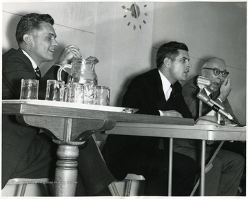 Three men seated at a table. The man in the center is Darrell V. McGraw, Special Assistant to Governor Hulett Smith.