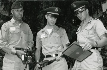 Men in their uniforms looking over a document. L. Stanley Farr, Professor of Physics on the left.