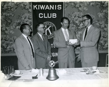 'Gasorama Chairman Kenneth Kincaid 'far right' presenting Gasorama tickets to, left to right, Ward Stone, Collins Veach, and Bob Yagley for the Kiwanis Club's annual Gasorama to be held at a local gas station on Tuesday June 17th.  All club members were presented with tickets which will be sold to the public to help finance the Kiwanis youth program.  The ticket purchaser will obtain gas at the regular station price by cashing in his tickets for the above day.  The service station manager is donating his profit for that day.'
