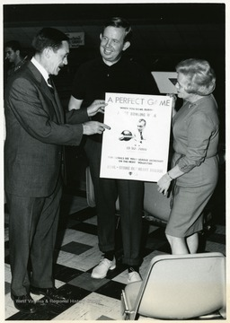 Terry Thomas and Jack Fleming with an unidentified woman at a bowling alley.