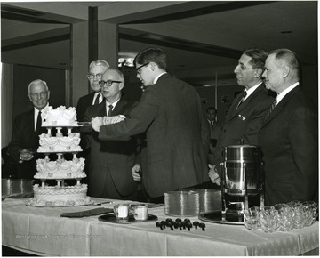 'Scene from the Febuary 7, 1968 reception celebrating the official close of the 100th Anniversary year shows from left to right: Maurice Brooks, member of the 100th Anniversary executive committee; Festus Summers, WVU Historian; Donovan H. Bond, executive director of the 100th Anniversary observance; Jim Mullendore, president of WVU student body; Gus Comuntzis, whose restaurant, 'Comuntzis', baked the birthday cake; and Sam Boyd, Jr., member of the 100th Anniversary executive committee'.