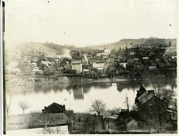 'View of Morgantown taken from the west side, showing old brick house on the west side, Business district at the Wharf. Shows the old firehouse at the Decker's Creek end of Walnut Street, and the old Academy tower on the left. Note the smoke at the mill at the end of Wharf Street.'