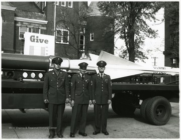 Amry men standing in front of a missle in their uniforms.