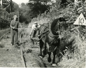 Two men use a horse drawn plow to dig ditches along the railroad tracks.