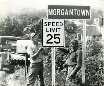 Mr. Smith (left) and Harry Franks (right) putting up a speed limit 25 sign on College Avenue.