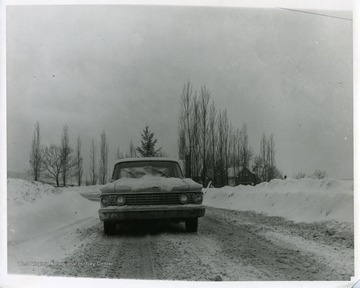 A car is parked in the middle of a road on a snowy winter day in Morgantown, West Virginia. A house can be seen in the background behind some trees.