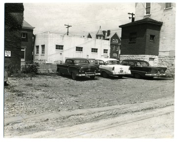 Three cars are parked in a parking lot on Moreland Street where Spruce and Pleasant Street Parking Lot is now.