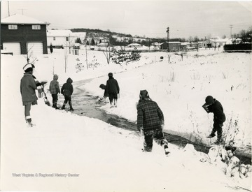 A group of children playing in the snow behind Collins Ferry Road next to a stream.