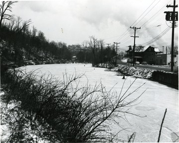 South University Avenue near city limits and Cobun Creek in winter. The buildings along the road are Morgantown Hydraulics, Dwelling, Core's Grocery, and the last house up the hill is the Bruce Ross House.